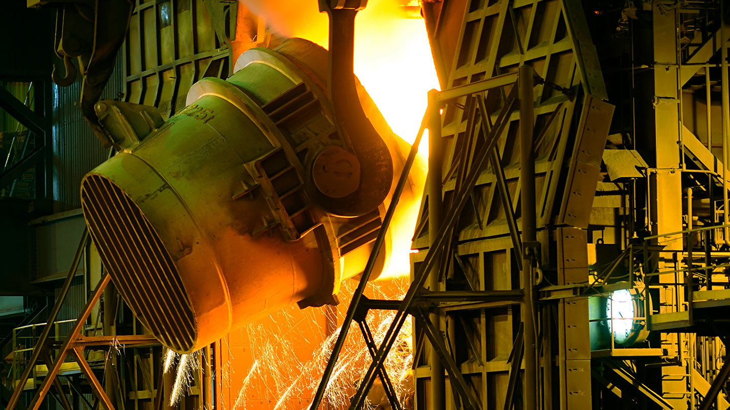 Industrial ladle pouring molten metal into a furnace in a metal production operation.