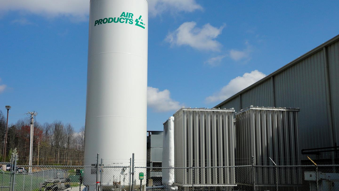 Air Products cryogenic liquid tank and vaporizer beside a manufacturing facility